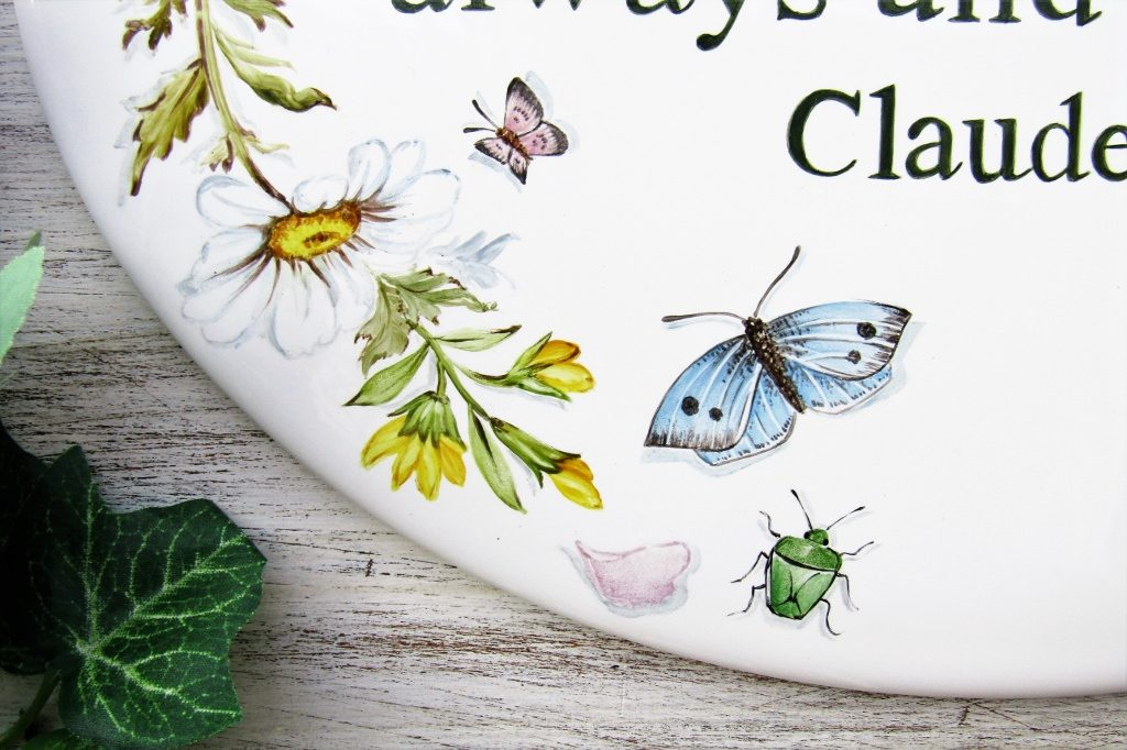 detail of hand painted butterfly and flowers on garden sign