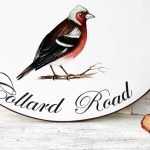 Closeup picture of chaffinch bird and house address sign